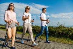 Gehendes Familientraining des Nordic an der Küste Lizenzfreie Stockbilder