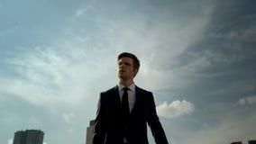 Gehendes Freien des jungen selbstbewussten jungen Geschäftsmannes, Erfolgskonzept, Stadt stockfotografie