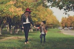 Gehendes Händchenhalten der Mutter und der Tochter am Park lizenzfreies stockbild