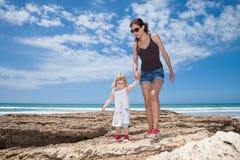 Gehendes Händchenhalten der Mutter und des Kindes nahe bei Ozean Stockbild