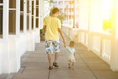 Gehendes Händchenhalten des Vaters und des Kindes Stockfoto