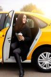 Gehendes herausgekommenes gelbes Taxi des reizend Brunette Lizenzfreies Stockbild
