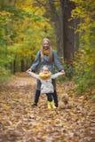 Gehendes im Herbstpark, gelbe Leben herum aufwerfen der Mutter und der kleinen Tochterblondine Stockbilder