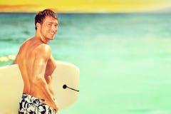 Gehendes Surfen des Surfermannes auf Sommerstrand Stockfotos