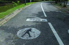 Gehendes Symbol des Mannes auf Straßenhintergrund Stockfoto