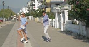 Gehendes Tanzen der jungen Frau und des Mannes und Anwendung der Tablette auf der Straße Saloniki, Griechenland stock video