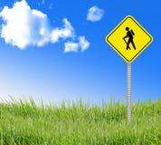 Gehendes Zeichen auf grünem Gras und blauem Himmel. Lizenzfreies Stockfoto