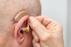 Gehoorapparaat in het oor van de oude oude mens royalty-vrije stock afbeelding