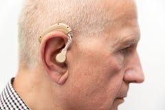Gehoorapparaat in het oor van de oude oude mens royalty-vrije stock fotografie