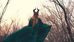 Gehoornde vreemdeling in lange smaragdgroene zijdekleding diep in bos alleen met magische in hand stok, het vreselijke vampier ve stock videobeelden