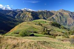 Gehucht op de groene helling in de Pyreneeën stock afbeelding