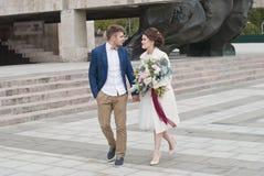 Gehuwd enkel houdend van paar in huwelijkskleding en kostuum Het gelukkige bruid en bruidegom het lopen lopen in de de zomerstad Royalty-vrije Stock Foto