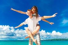 Gehuwd enkel jong gelukkig houdend van paar die pret op tropica hebben Royalty-vrije Stock Afbeeldingen