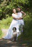 Gehuwd enkel lesbisch paar met hond in bos Royalty-vrije Stock Afbeeldingen
