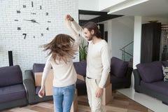 Gehuwd opgewekt jong paar die samen in woonkamer dansen stock fotografie