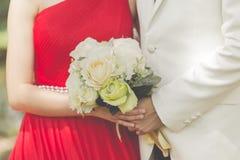 Gehuwde bruid en bruidegom die elkaar met een boeket van F omhelzen Royalty-vrije Stock Afbeeldingen