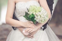 Gehuwde bruid en bruidegom die elkaar met een boeket van F omhelzen Royalty-vrije Stock Foto
