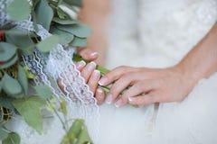 Gehuwde handen van een bruid, de enkel, een bruids boeket is naast stock foto