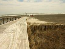 Gehweg über den Dünen zum auf den Strand zu setzen Stockfotografie