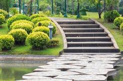 Gehweg über dem See, der zu konkrete Schritte durch den Park führt Lizenzfreie Stockfotos
