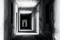 Gehweg in verlassenem Gebäude mit furchtsamer Frau nach innen Lizenzfreies Stockfoto