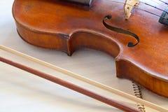 Geigenkampf und -bogen auf Musikbuch Lizenzfreies Stockbild