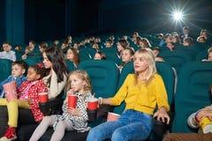 Geinteresseerde meisjes die op nieuwe film in de bioskoop letten Royalty-vrije Stock Fotografie