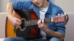 Geinteresseerde tiener die akoestische gitaar, amateur muzikale hobby, vrije tijd spelen stock video