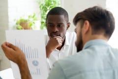 Geinteresseerde zwarte cliënt die aan financiële adviseur luisteren explainin royalty-vrije stock afbeeldingen