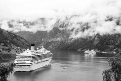 Geiranger,挪威- 2010年1月25日:在口岸靠码头的客轮 游轮在挪威海湾 目的地玻璃扩大化的映射旅行 图库摄影