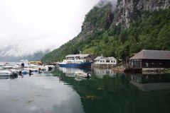 Geiranger,挪威- 2010年1月25日:村庄房子,小船在海在山风景怀有 水运输,船 旅行 免版税库存照片