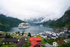 Geiranger,挪威- 2010年1月25日:船在多云天空的挪威海湾 远洋班轮在村庄港口 旅行目的地, 库存图片