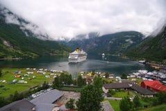 Geiranger, Noorwegen - Januari 25, 2010: vakantie, reis, zwerflustschip in Noorse fjord op bewolkte hemel Lijnboot in dorp Ha royalty-vrije stock fotografie