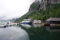 Geiranger Norge - Januari 25, 2010: byhus, fartyg i havshamn på berglandskap Vattentransport, skyttlar Resor royaltyfria foton