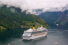 Geiranger, Norway - January 25, 2010: adventure, discovery, journey. Cruise ship in norwegian fjord. Passenger liner docked in por. T. Travel destination tourism stock photo