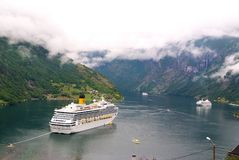 Geiranger, Norway - January 25, 2010: travel destination, tourism. Cruise ship in norwegian fjord. Passenger liner docked in port. Adventure discovery, journey stock photo