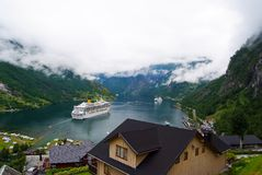 Geiranger, Norway - January 25, 2010: travel destination, tourism. Ship in norwegian fjord on cloudy sky. Ocean liner in village h. Arbor. Travel destination stock image