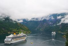 Geiranger, Norway - January 25, 2010: vacation, trip, wanderlust. Cruise ship in norwegian fjord. Passenger liner docked in port. Travel destination tourism Royalty Free Stock Images