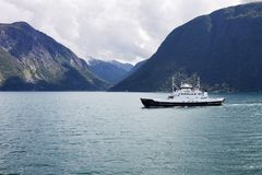 A fjord with a floating ship in Norway. A landscape with the mountains and fjords is a typical Norwegian landscape stock photo