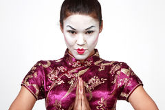 Geisha. A young beautiful Asian woman head portrait with serious expression in her pretty face wearing Geisha make up, holding her hands together in front of her Royalty Free Stock Images