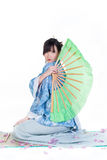 Geisha in blue kimono. Beauty geisha in blue kimono sit on mat with big green fan isolated on white background Stock Photos