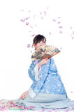 Geisha in blue kimono. Beauty geisha in blue kimono sit on mat with fan isolated on white background Royalty Free Stock Image