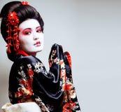 Geisha bonito joven en kimono con Sakura y el DES rojo de la decoración Imagen de archivo