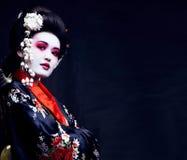 Geisha bonito joven en kimono con Sakura y la decoración imagen de archivo