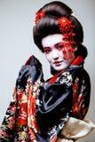 Geisha bonito joven en kimono en el fondo blanco Foto de archivo libre de regalías