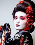 Geisha bonito joven en kimono negro entre Sakura, cierre asiático del ethno para arriba Imágenes de archivo libres de regalías