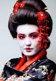 Geisha bonito joven en kimono negro entre Sakura, cierre asiático del ethno para arriba Foto de archivo libre de regalías