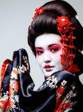 Geisha bonito joven en kimono negro entre Sakura, cierre asiático del ethno para arriba Imagenes de archivo