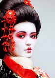 Geisha bonito joven en kimono negro entre Sakura, ethno asiático Fotografía de archivo libre de regalías