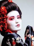 Geisha bonito joven en kimono negro entre Sakura, ethno asiático Foto de archivo